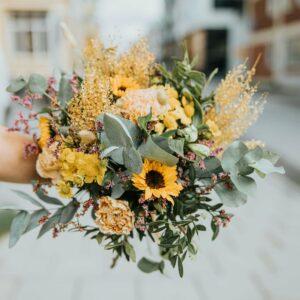 Höstbuketten med höstiga blommor, t.ex. solrosor och strån